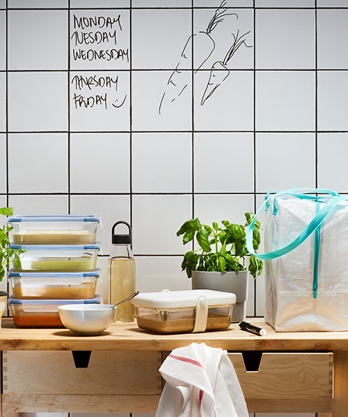 Various food storage items such as a water bottle and containers are placed on a wooden kitchen countertop. There are a couple potted plants around the items as well.
