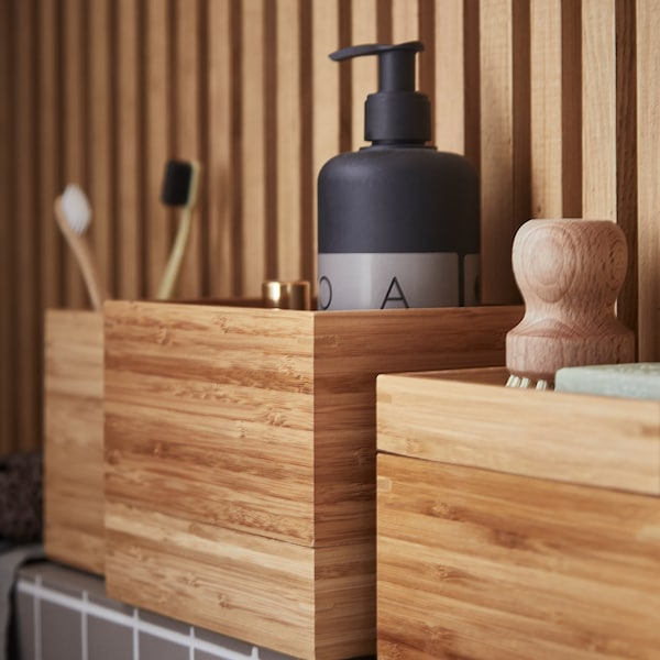 Various IKEA DRAGAN bamboo boxes are placed against a bamboo wall with vents. They are filled with bathroom products.