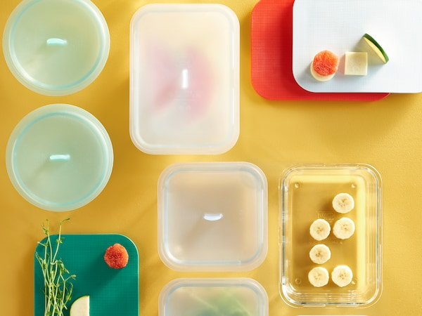 Various plastic food containers against a mustard coloured background.