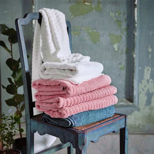 Various towels in gray, pink and white stacked on a dark gray wooden chair, set against a rustic green-gray wooden door.