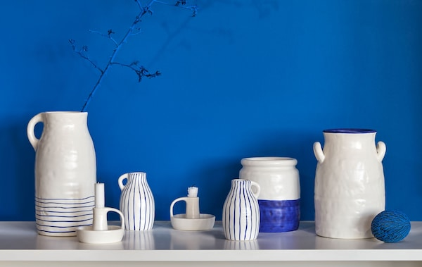 Various two-colour ceramic vases, jugs and candleholders in a rustic, handmade quality, placed on a side-table top.