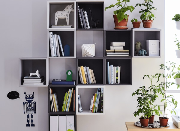 Various white and black cube shelves mounted to the wall holding books, Dala horses, and plant pots.