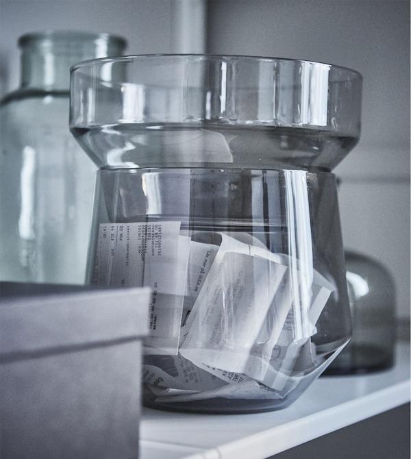 Vase IKEA PS 2017 en verre transparent gris contenant des reçus.