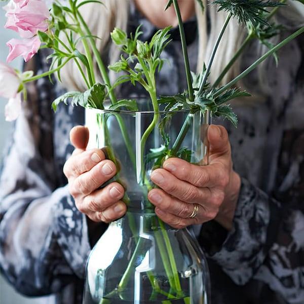 Vase OMTÄNKSAM avec des tiges vertes magnifiquement arrangées dans les mains d'une femme âgée.
