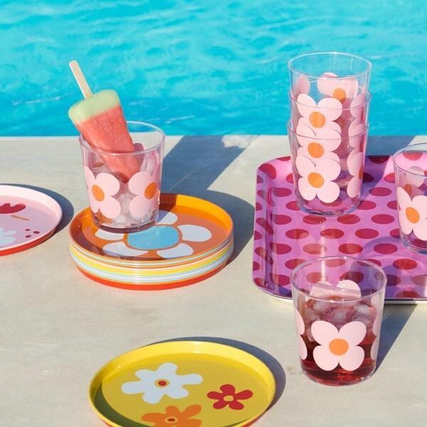 Vasos y bandejas SOMMAR 2019 con estampados de flores en colores mezclados junto a la piscina.