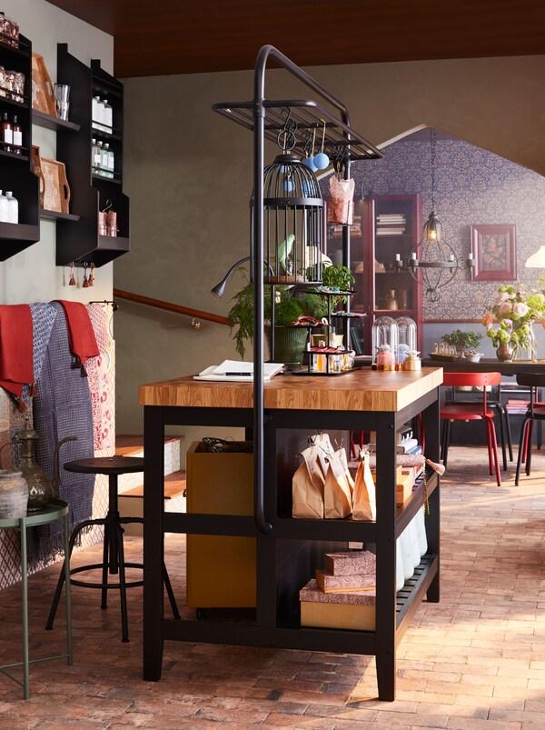 Vastaanottoalueena toimii VADHOLMA-keittiösaareke ja KULLABERG-baarituolit. Myynnissä olevia tuotteita on aseteltu saarekkeen hyllyille ja nostettu ripustuskoukkuihin.