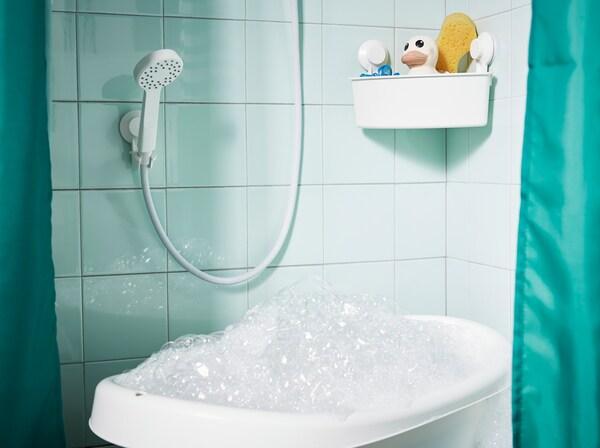 Vauvan kylpyamme täynnä kuplia suihkussa, jossa on vihreät laatat ja vihreä suihkuverho. Sen yläpuolelle on sijoitettu käsisuihku.