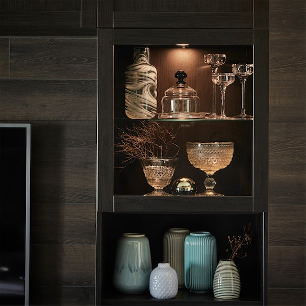 VAXMYRA LED spotlight in aluminium-colour, situated in a glass-door cabinet and highlighting various vases and fine glasses.