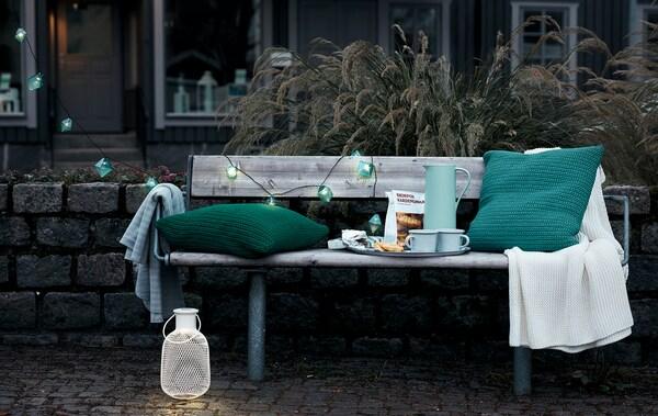 Вечірній час, лавка на вулиці з кавовим підносом, подушками, пледом та декоративним освітленням.