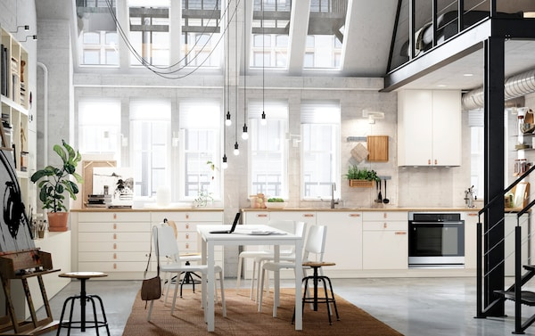 VEDDINGE smooth white cabinet doors arranged across an entire kitchen wall in an open space loft apartment.