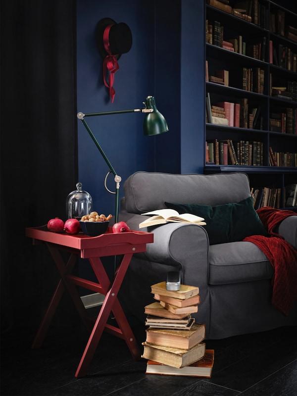 Vedle útulně vypadajícího křesla EKTORP s červeným stolkem a zelenou lampou jsou na hromádce naskládané knihy.