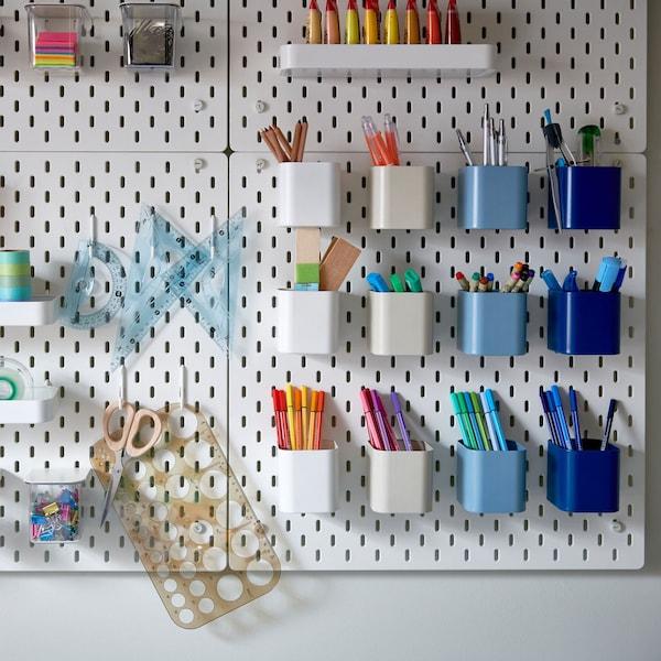Veel ophangborden met gaten waaraan opbergers in verschillende kleuren hangen met kleurrijke pennen, paperclips en tape.