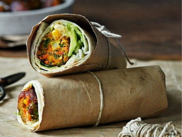 Vegetable wraps on a wooden chopping board, tied with string