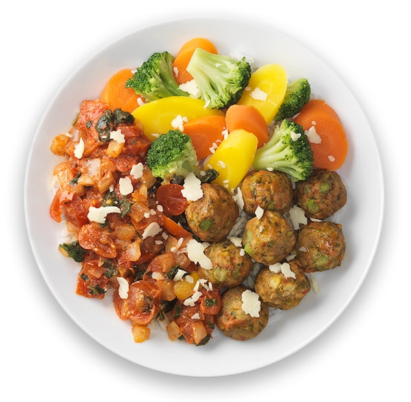 Veggie balls with rice, tomato spinach ragout and vegetables on a white plate.