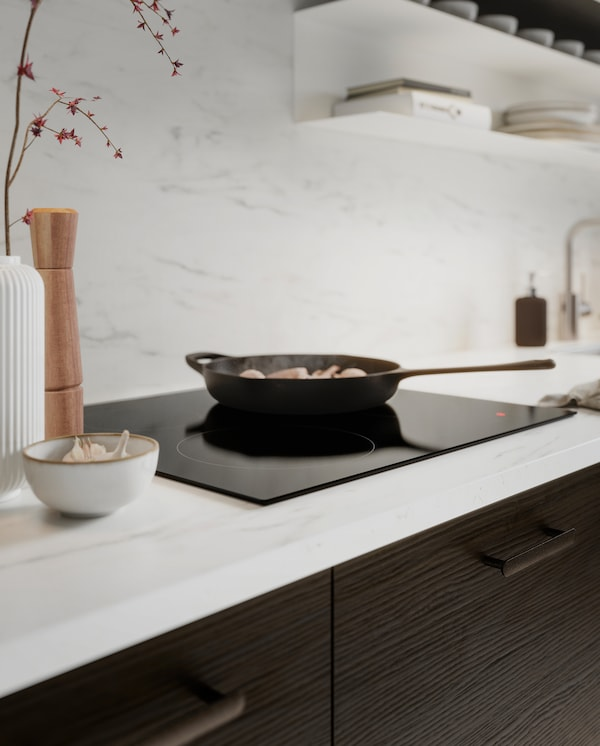 Veggplate og benkeplate i hvitt marmormønster, kjøkkenfronter i mørkebrunt askemønster, en induksjonstopp og ei støpejernspanne.