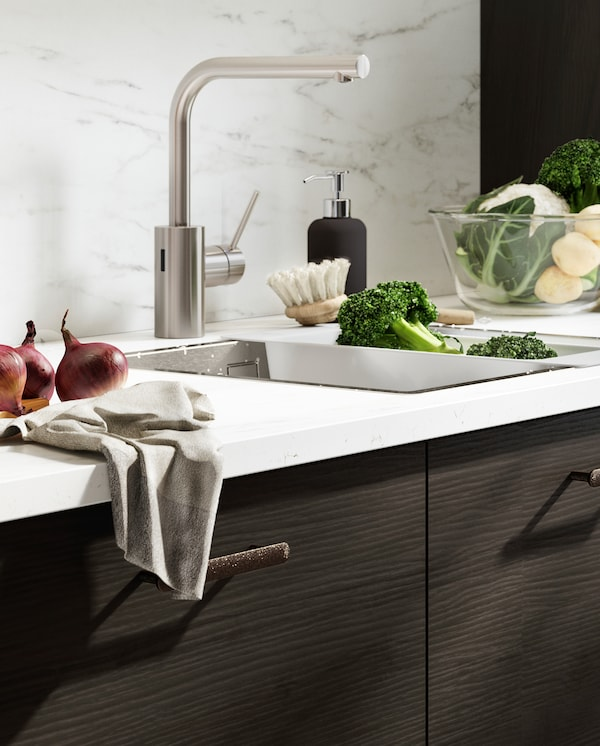 Veggplate og benkeplate i hvitt marmormønster, kjøkkenfronter i mørkebrunt askemønster og et blandebatteri i rustfritt stålfarge.
