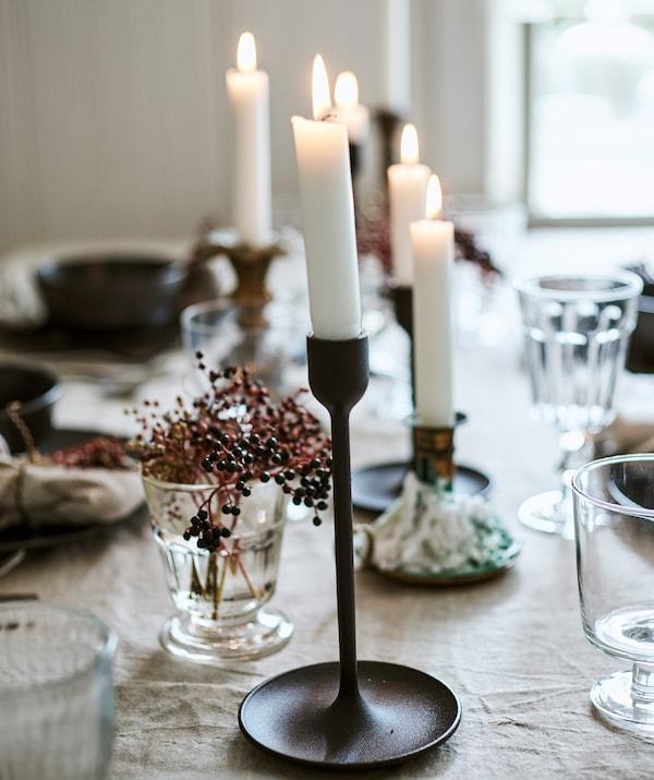 Velas acesas em vários porta-velas pretos e cor de latão numa mesa coberta por uma toalha de linho, copos e bagas numa jarra.