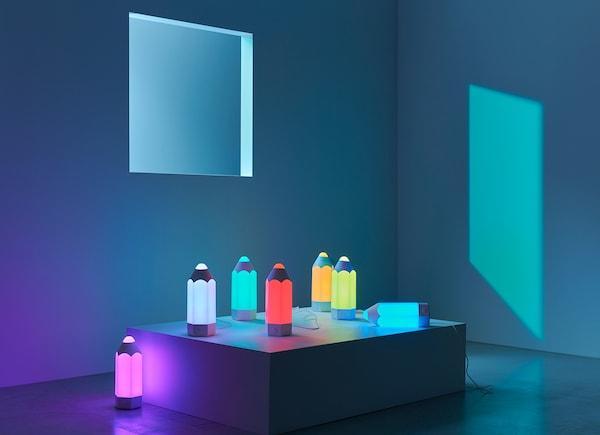 Velik broj PELARBOJ stolnih lampi različitih boja na stalku u sobi.