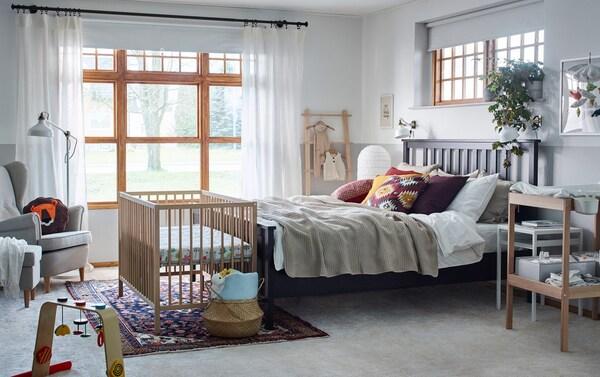 Velika bela spavaća soba s drvenim detaljima opremljena je za par i bebu, uključujući SNIGLAR krevetac.