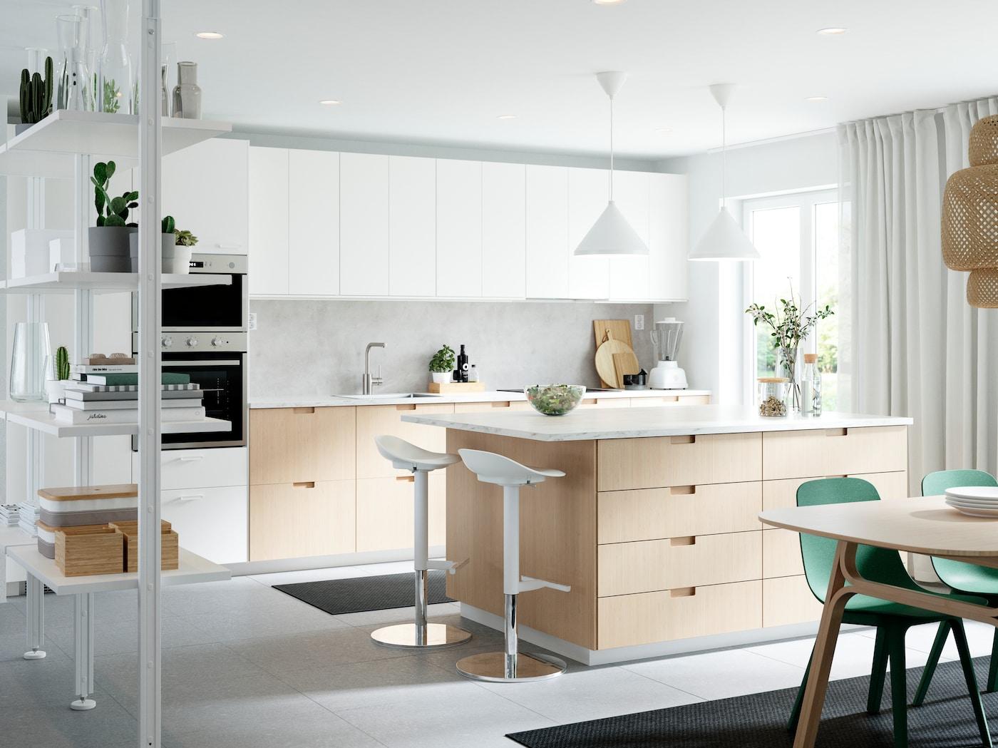Velika kuhinja s frontovima od nerđajućeg čelika, radnim pločama od hrasta/furnira, plavim radnim lampama i začinima u posudama.