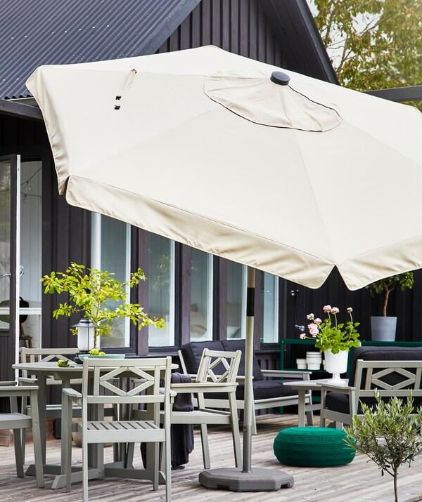 Veliki suncobran u bež boji na terasi sa sivim baštenskim nameštajem i biljkama.
