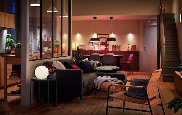 Veľká miestnosť s kuchyňou, jedálňou a obývacou izbou osvetlená viacerými rôznymi svietidlami.