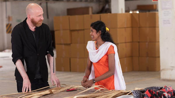 Veľká miestnosť v indickej továrni, kde sa švédsky dizajnér IKEA rozpráva s indickou remeselníčkou o banánových vláknach.