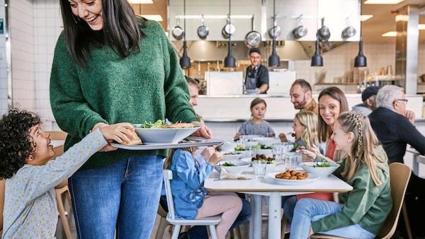 Velká rodina s dětmi sedící za stolem s jídlem, v popředí žena s tácem a malým dítětem.