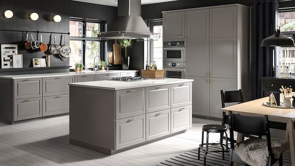 Velká šedá kuchyně s kuchyňským ostrůvkem uprostřed jídelním stolem v kombinaci buk/bílá s černými židlemi a stoličkami.