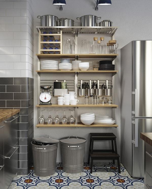 Veľké nástenné úložné riešenie s drevenými policami, nádobami, tyčami a mriežkami s kuchynským náčiním.