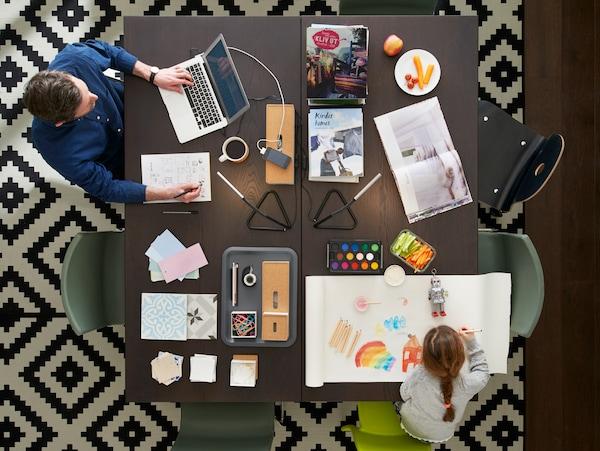 Velký stůl, z jedné strany sedí pracující muž s laptopem, z druhé strany je holčička, která si maluje.