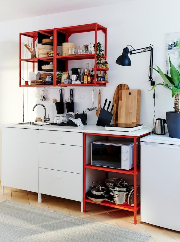 Veludstyret, lille køkken indrettet med en kombination af ENHET elementer – åben opbevaring i rød, lukket opbevaring i hvid.