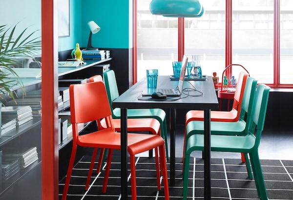 Vergadertafel met groene en rode stoelen