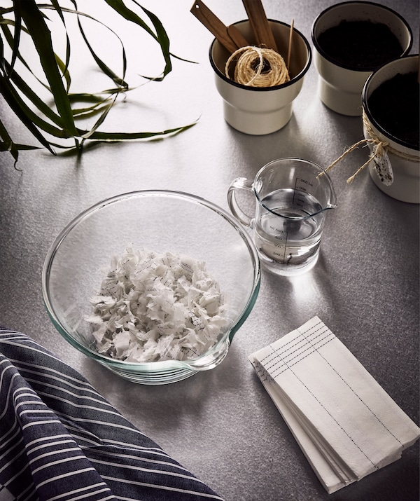 VERKLIGHET paper napkins, a big glass bowl with some shredded paper napkins inside and a jug of water beside it.