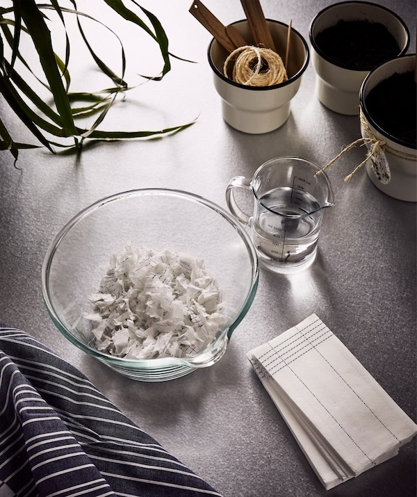 VERKLIGHET paper napkins, a large glass bowl with some shredded napkins and a jug of water next to it.