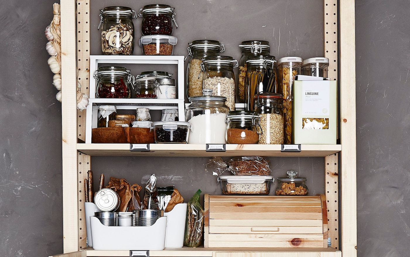 Verschiedene Lebensmittel in Vorratsbehältern in einem offenen Schrankregal