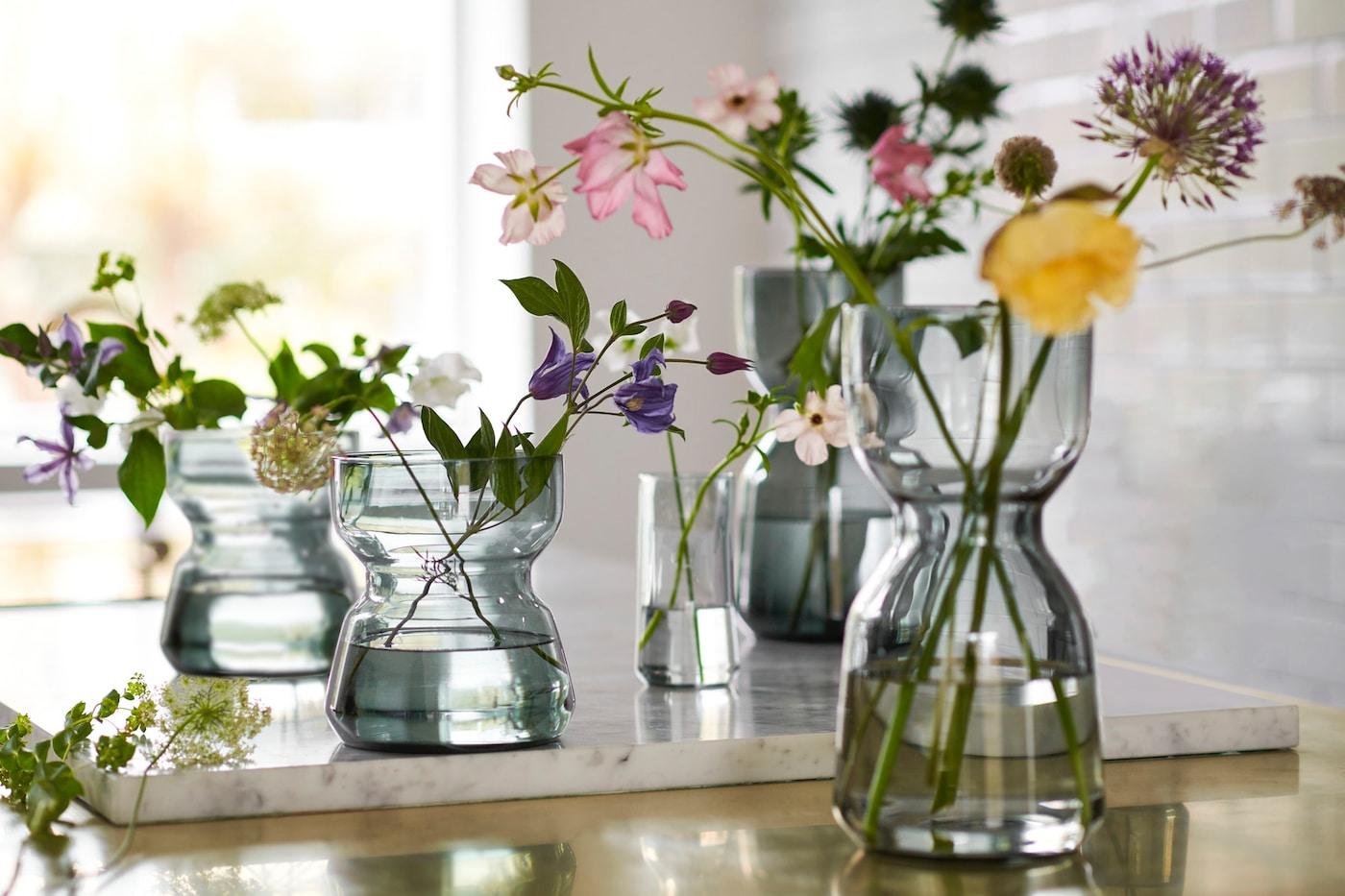 Verschiedene OMTÄNKSAM Vasen aus Klarglas, die mit frischen Blumen darin auf einer Arbeitsplatte stehen; alle zeichnen sich durch ihre charakteristische schmale Taille aus, durch die sich die Vasen gut greifen lassen