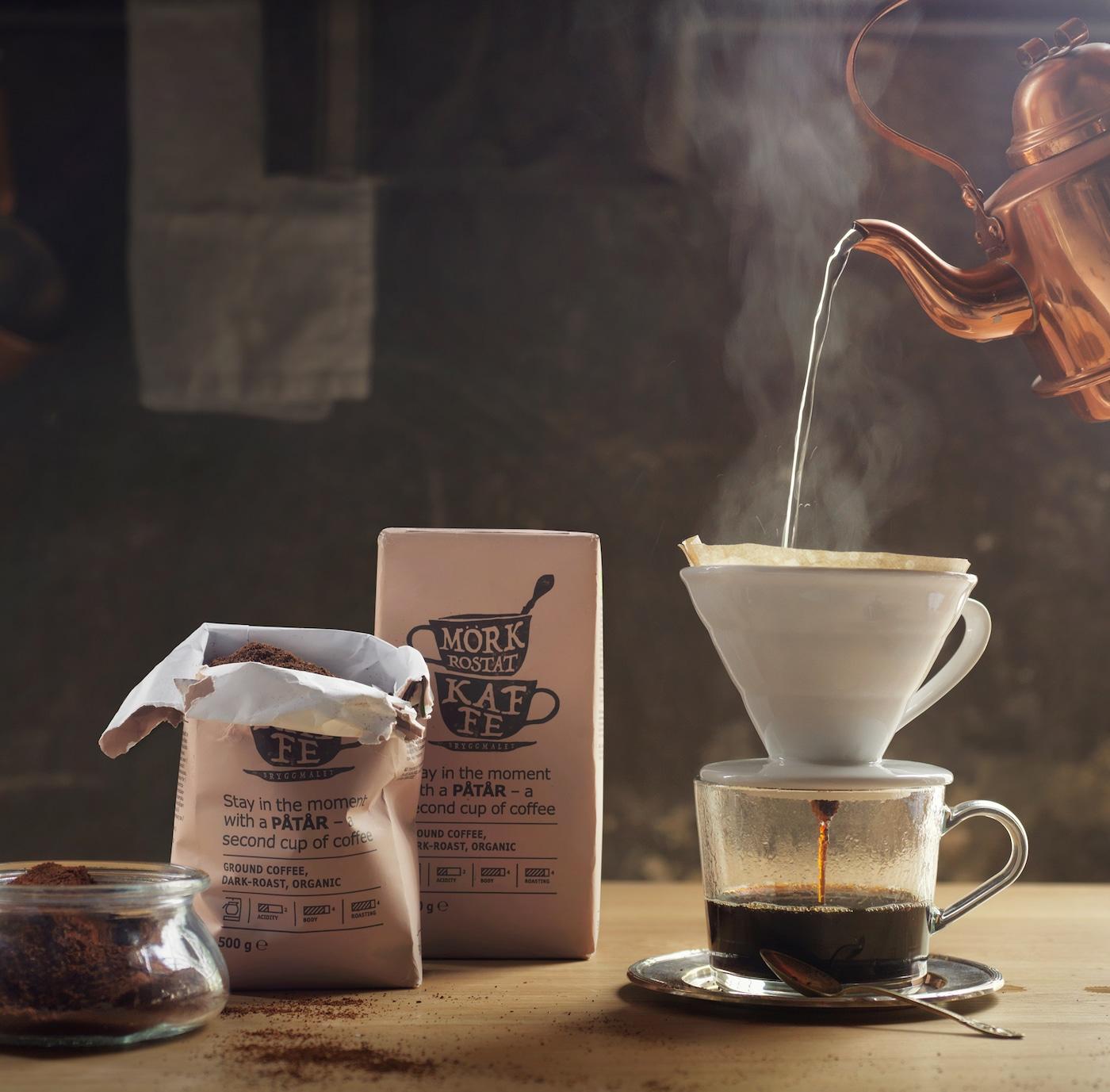 Verschiedene Packungen PÅTÅR Kaffee, daneben eine frisch aufgebrühte Tasse Kaffee