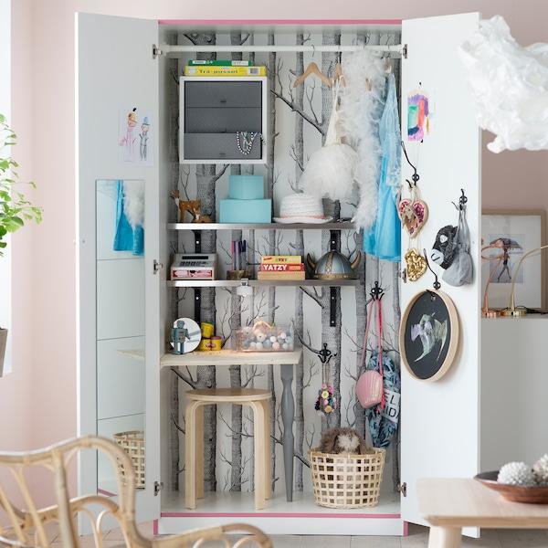 Versteckte Aufbewahrungsideen im Wohnzimmer sind der perfekte Einsatzort für einen alten Kleiderschrank. Hier kannst du Spielzeug einfach verschwinden lassen, wenn die Spielzeit vorbei ist. Bei IKEA findest du jede Menge erschwingliche Kleiderschränke wie PAX in Tanem Weiß mit zwei weißen Türen.