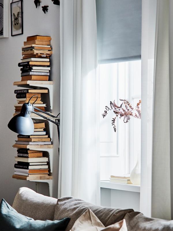 Vertikale Bücherverwahrung mit vier SIBBHULT Konsolen und Böden neben einem Fenster mit transparenten Gardinen.