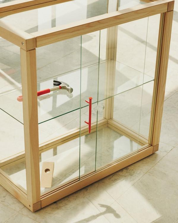 Vese un martelo vermello dentro dun armario de cristal con marco de madeira, e a súa sombra reflíctese no chan en fronte del.