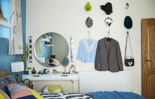 Vêtement et accessoires accrochés au mur de la chambre.