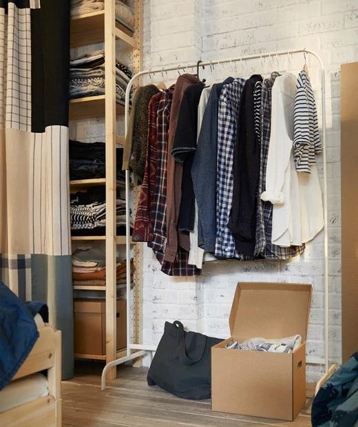 Vêtements accrochés au portant MULIG inséré dans un espace penderie près duquel on trouve des étagères, le tout placé contre un mur de briques.