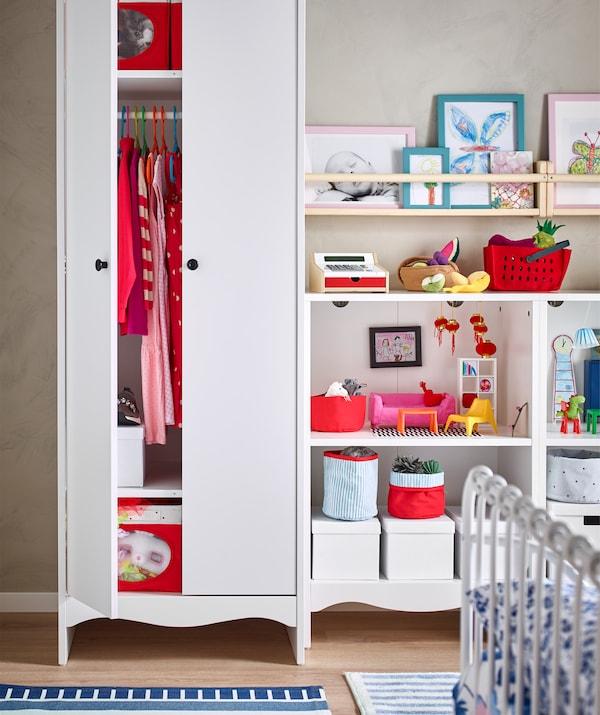 Vêtements et boîtes rouges dans une armoire-penderie blanche toute en hauteur; livres, jouets et boîtes sur une étagère ouverte.