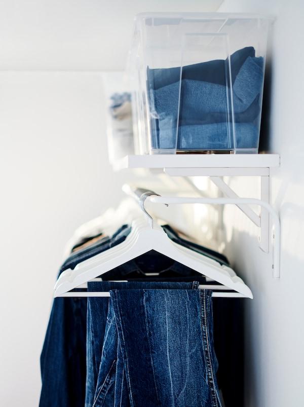 Vêtements pliés dans des bacs transparents rangés sur une tablette BERGSHULT. Juste en dessous, des vêtements accrochés sur des cintresBUMERANG.