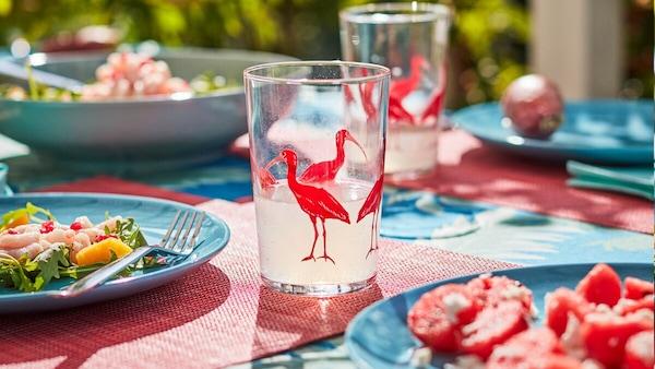Vibráló színekben pompázó, egzotikus mintákkal díszített kiegészítőkkel terített asztal.