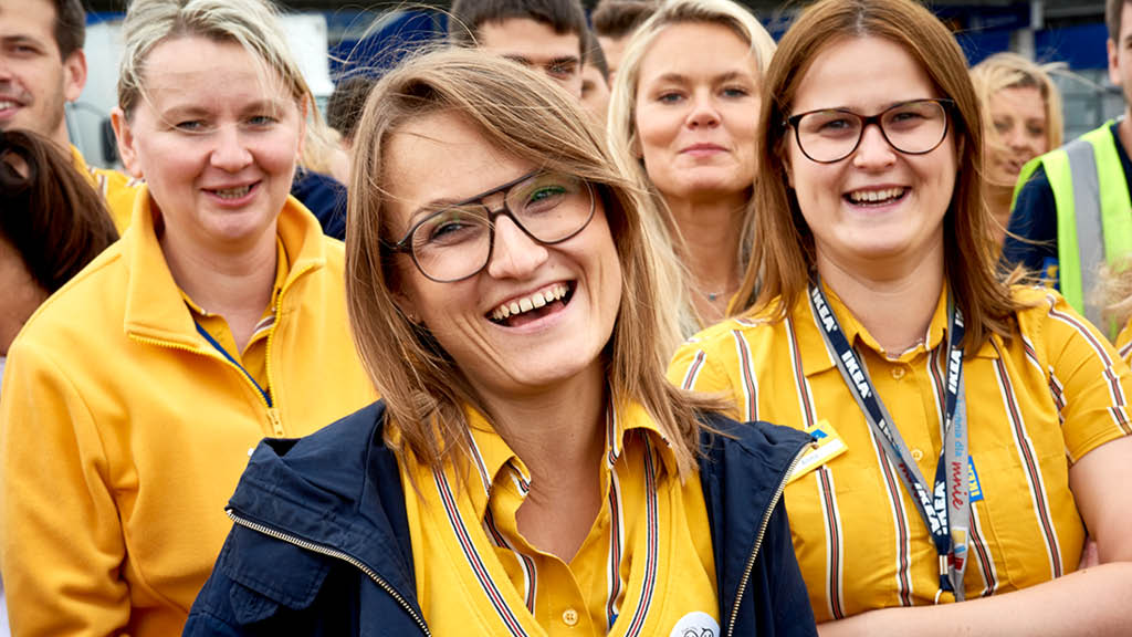 Viele IKEA Mitarbeiter lachen, im Vordergrund steht eine junge Frau mit Brille