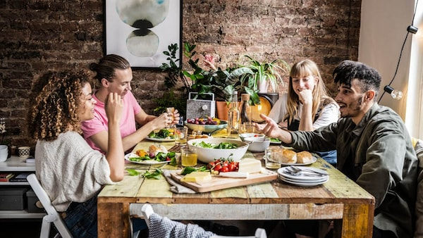 Vier Freunde sitzen gemeinsam am Tisch und Essen