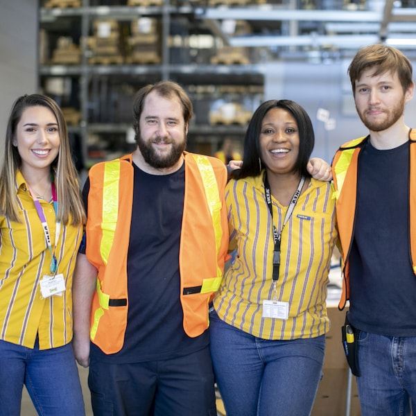 Vier Menschen in unterschiedlichen IKEA Mitarbeiteruniformen stehen lächelnd nebeneinander.