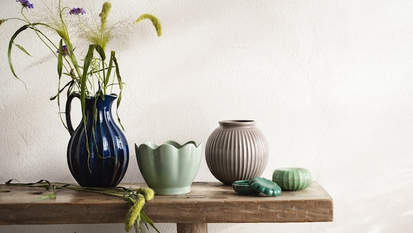 Vier Vasen im traditionellen Design, die auf einer Holzbank stehen.